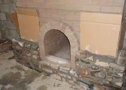 Fresh stone masonry facing a masonry fireplace.
